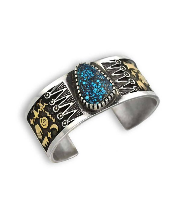 Sterling silver and gold cuff bracelet by Native American artist Arland Ben with a large natural turquoise center stone; Located at Kenny's on the Plaza in Santa Fe New Mexico.